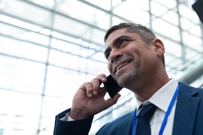 白种人商人特写镜头谈话在自动扶梯的手机 库存图片