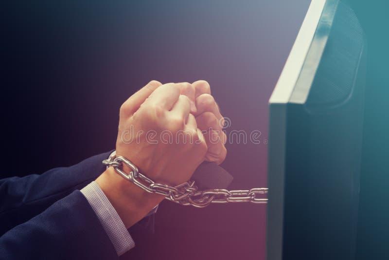 白种人商人的手使上瘾到互联网并且锁了与铁链子腕子、智能手机互联网瘾和奴隶 免版税库存图片