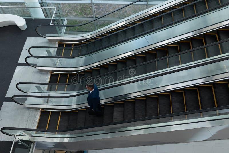 白种人商人谈话在手机,当移动下来在自动扶梯时 免版税库存图片