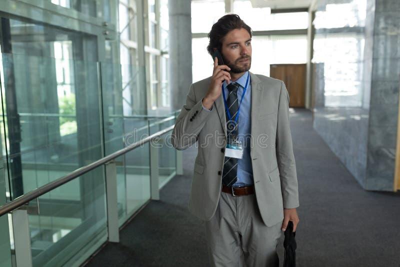 白种人商人谈话在手机,当走在走廊时 免版税图库摄影