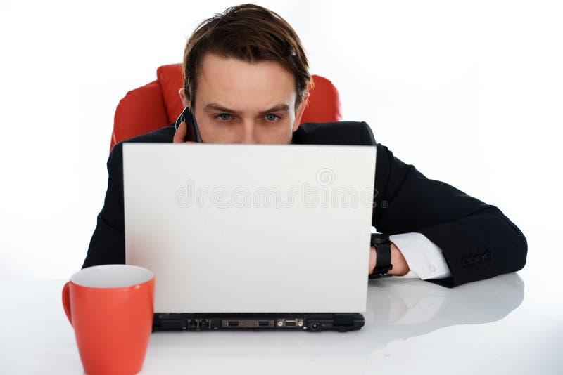 白种人商人谈话在电话在他的书桌 免版税库存照片