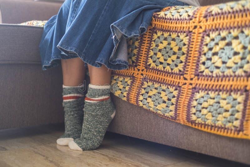 白种人在家穿一个对愉快和滑稽的袜子的妇女腿和脚在冬天期间 来自窗口光,关闭  免版税库存照片