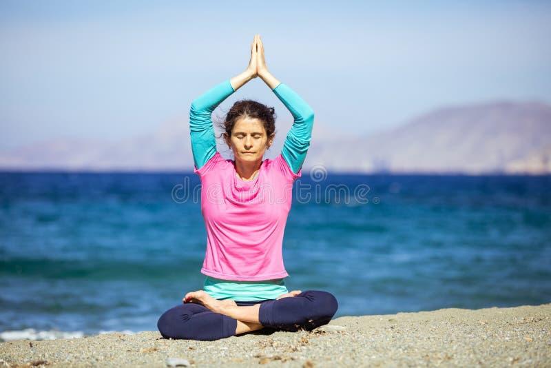 白种人在海滩的年轻女人实践的瑜伽 库存照片