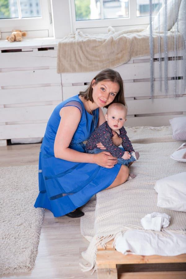 白种人坐在床附近的母亲和女儿 图库摄影