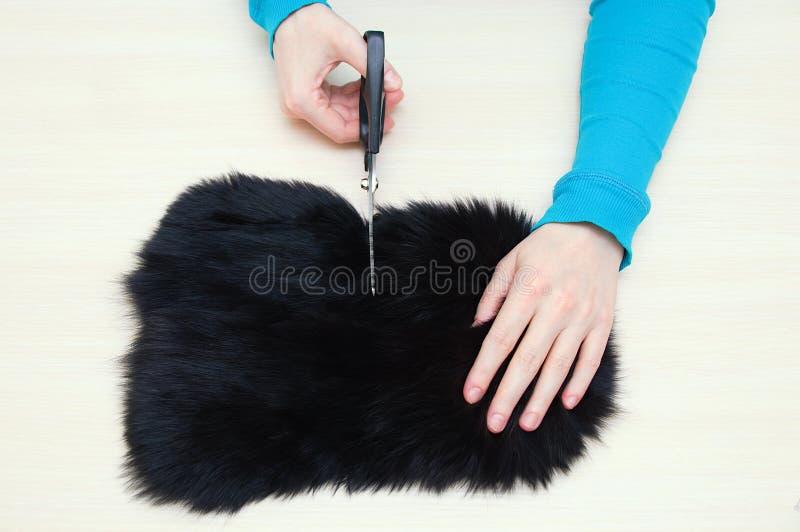 白种人女孩切开与黑剪刀的毛皮皮肤在桌上 库存照片