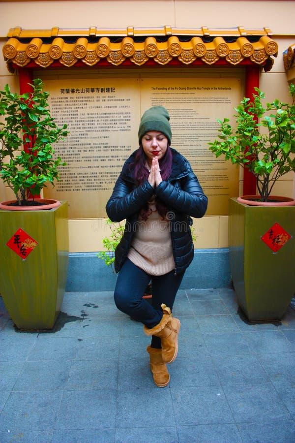 白种人女孩在一个冬日 祷告,凝思的位置,奇怪 在东亚佛教寺庙之外 库存图片