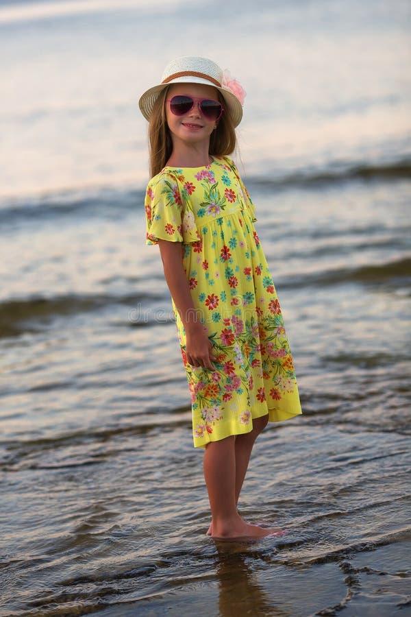 白种人女孩微笑愉快在晴朗的夏天或春日外面在公园由湖 t 库存照片