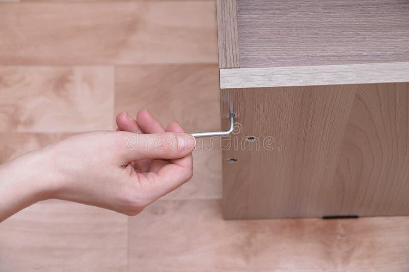 白种人女孩拧紧有钥匙的一个螺丝在家具 r 免版税图库摄影