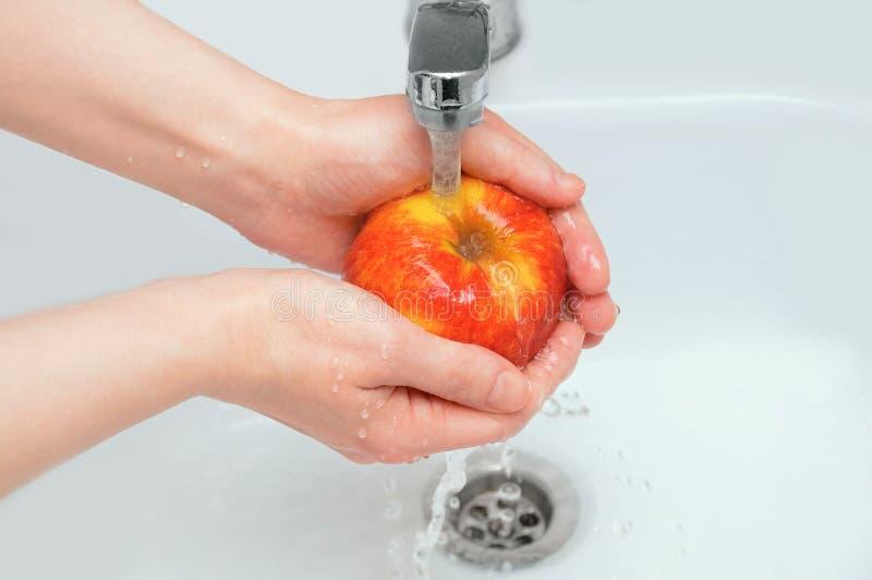 白种人女孩洗涤一个苹果在淌淌水下 免版税库存图片