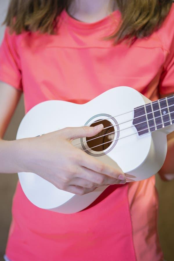 白种人女孩的手特写镜头有户内小吉他的 库存照片