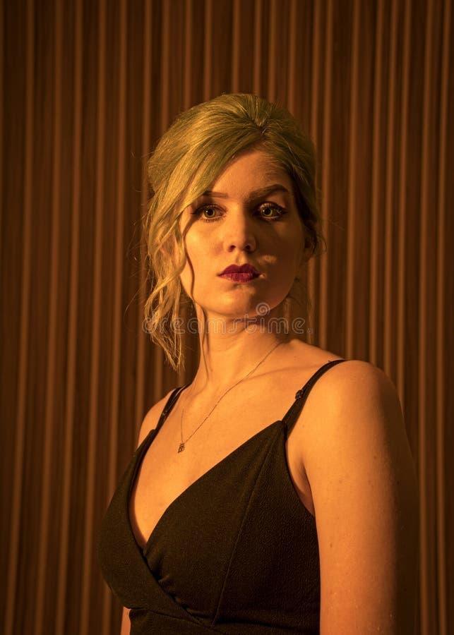 白种人女性模型,年龄22,蓝色染头发,红色嘴唇,黑色有带子的上面,橙色过滤器 顶头肩膀 免版税图库摄影