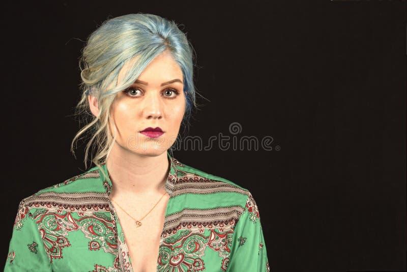 白种人女性模型,年龄22,蓝色洗染了头发,红色嘴唇,绿色和红色衬衣 查出在黑色背景 上部躯干 前的腹部 免版税库存照片