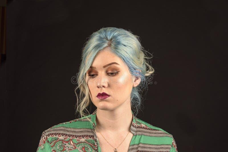白种人女性模型,年龄22,蓝色洗染了头发,红色嘴唇,绿色和红色衬衣 查出在黑色背景 顶头肩膀 免版税图库摄影