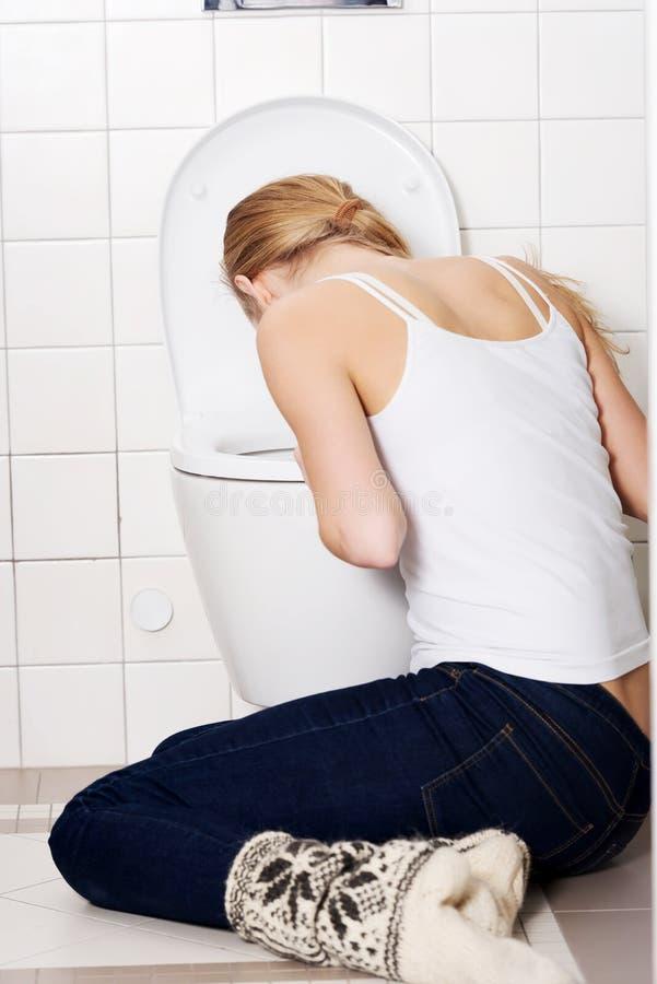 年轻白种人妇女在卫生间里呕吐。 免版税库存照片
