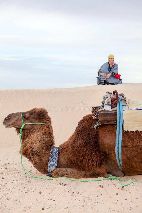 白种人妇女坐沙丘在沙漠 图库摄影