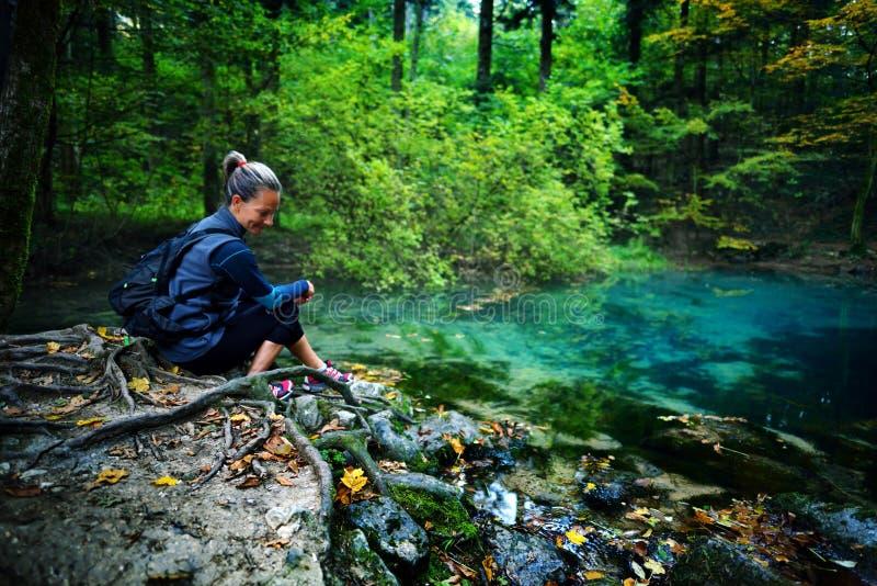 白种人妇女旅游放松由河,在森林里, Oc 免版税库存照片