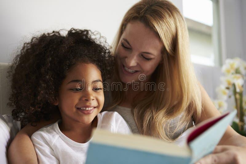 白种人妈咪和微笑的黑人女儿写入床,特写镜头 免版税库存图片