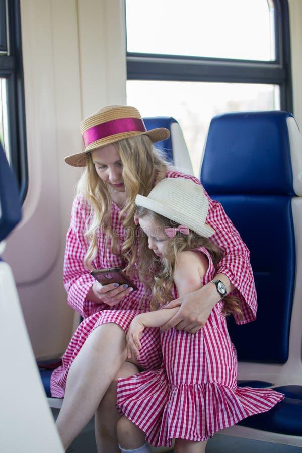 白种人小女孩画象有她的妈妈的有波浪发的帽子的使用在火车的一个智能手机 免版税库存图片