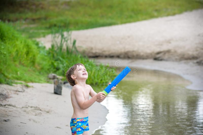 白种人小男孩画象演奏玩具和水泵在海滩的草帽的 免版税库存图片