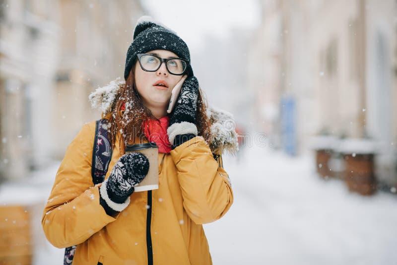 白种人少年妇女谈话在笑的电话举行一外带咖啡杯微笑 户外冬天画象  库存图片