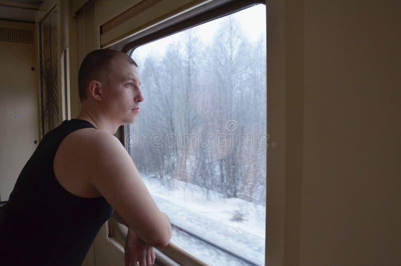 白种人年轻人坚持在列车车箱的窗口和神色在冬天积雪的风景的窗口 免版税库存照片