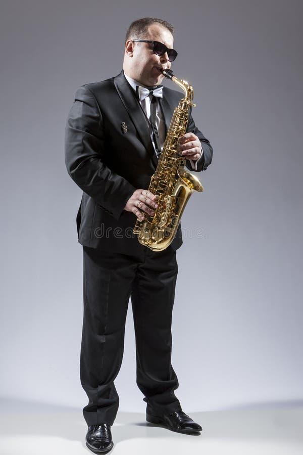 白种人成熟萨克管演奏员全长画象太阳镜的 免版税库存照片