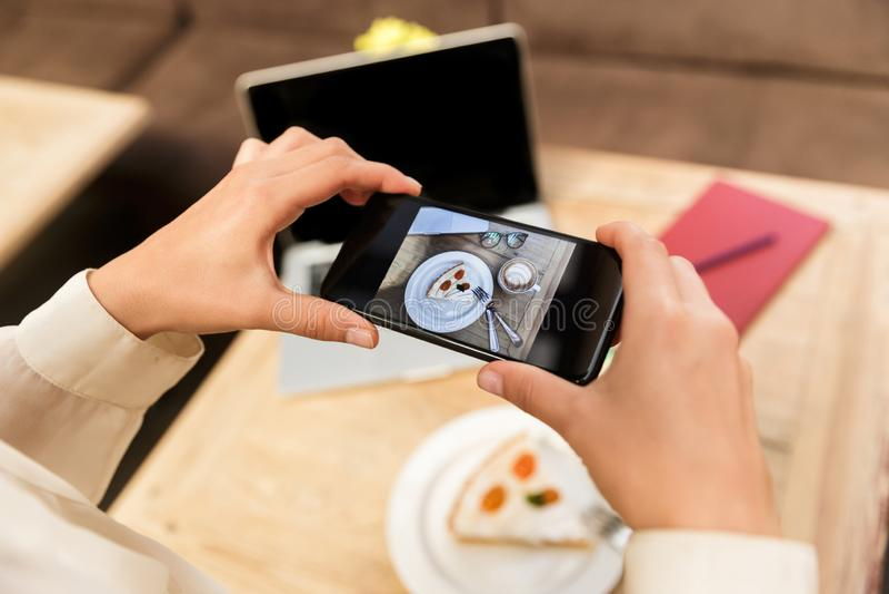 白种人拍摄在手机的妇女佩带的帽子播种的照片食物 库存图片