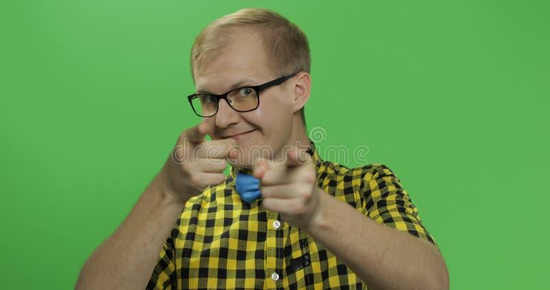 白种人时兴的人在照相机显示手指 黄色衬衣的人 图库摄影