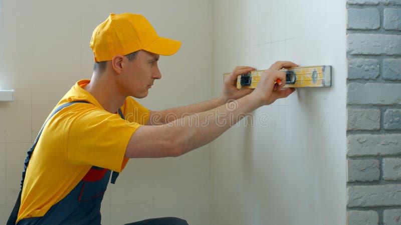 白种人有平实工具的建造者测量的墙壁 免版税库存图片