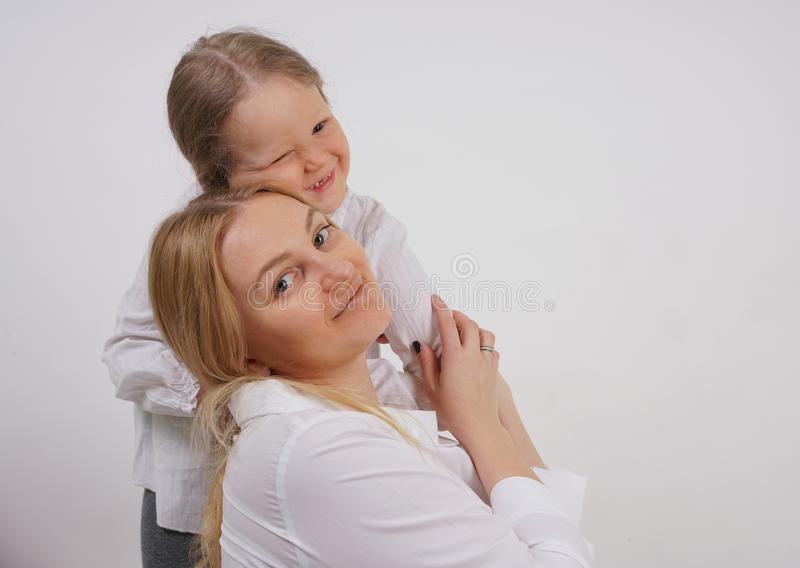 白种人母亲和女儿真正的家庭白色衬衫的在演播室背景中 免版税库存图片