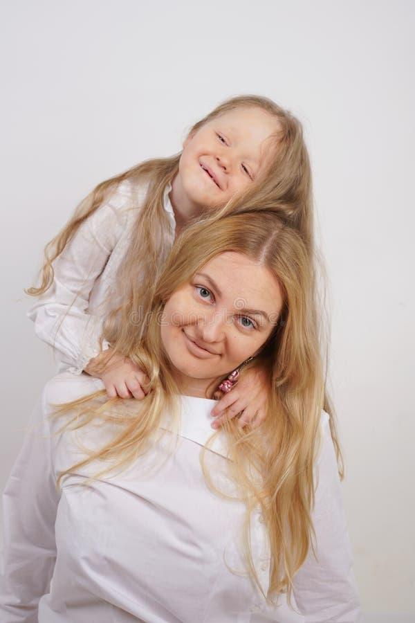 白种人母亲和女儿真正的家庭白色衬衫的在演播室背景中 免版税库存照片