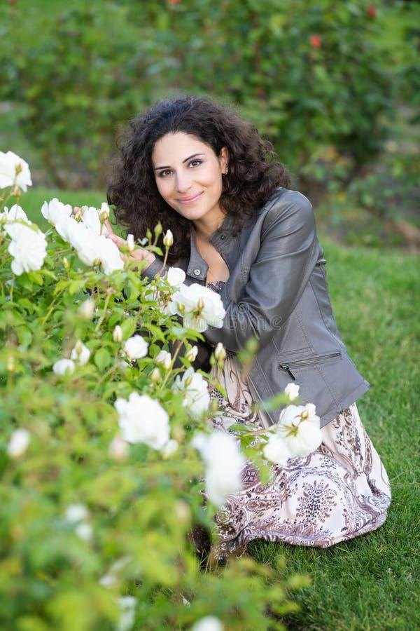 白种人深色的年轻女人坐绿草在一个玫瑰园里在黄色玫瑰丛附近,微笑与牙,看对 免版税库存图片