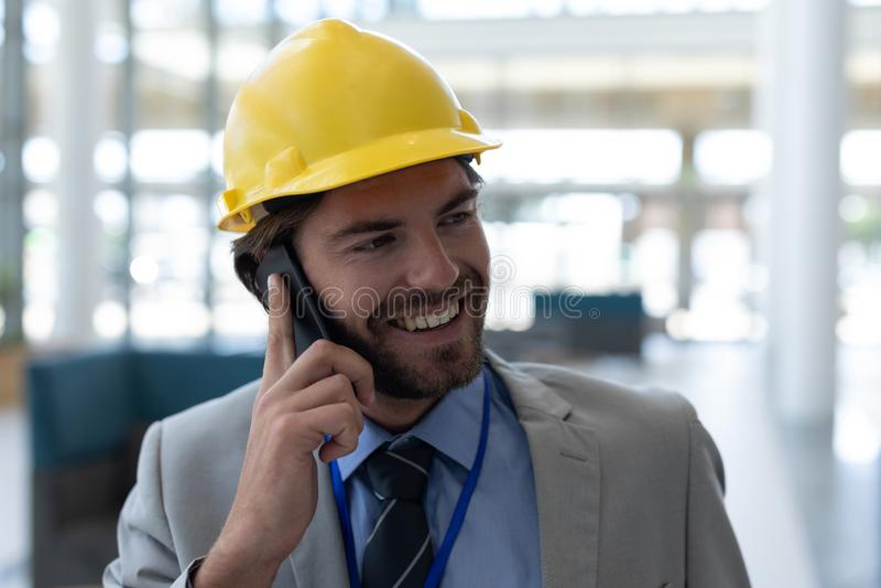 白种人男性建筑师谈话在手机在现代办公室 图库摄影