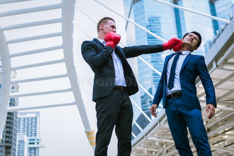 白种人男服黑色衣服和红色拳击手套拳打对亚裔人的面孔 免版税库存图片