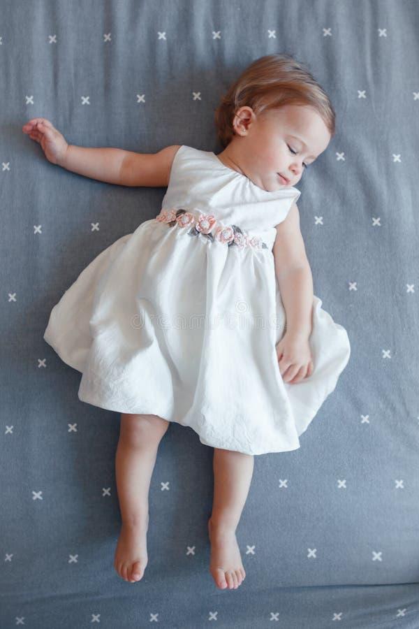 白种人白肤金发的女婴在说谎在灰色床单的白色礼服的一岁在卧室,从上面的看法 免版税库存图片