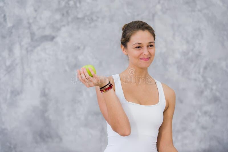 白种人美丽的健康运动嬉戏女孩在训练以后吃绿色苹果和看照相机 免版税库存图片