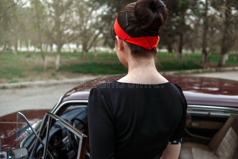 白种人美丽的少女画象在一辆减速火箭的汽车坐的黑葡萄酒礼服的 免版税库存照片