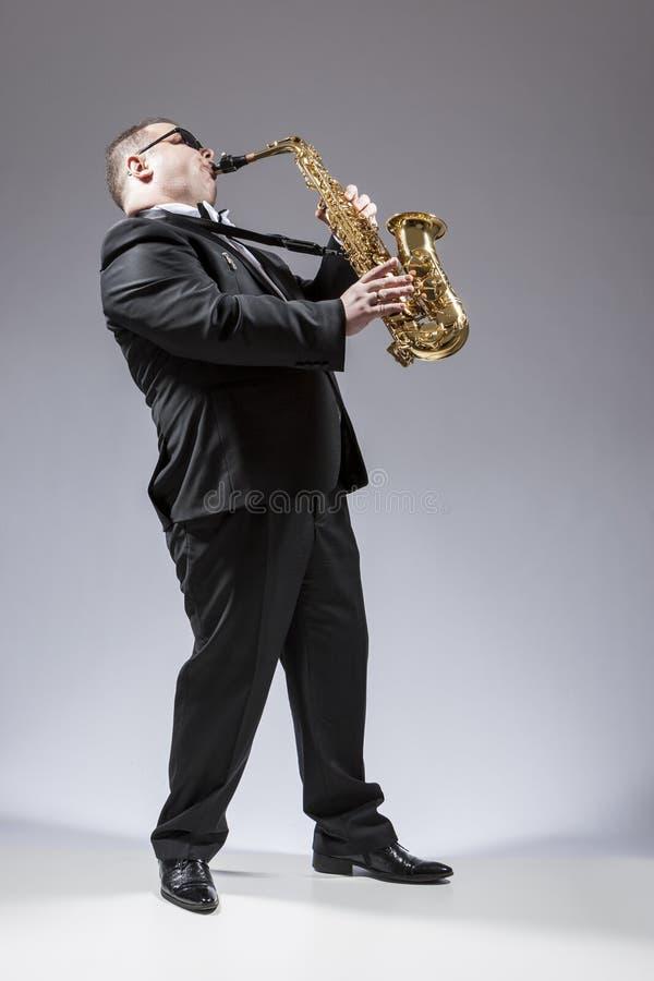 白种人萨克管演奏员全长画象弹奏仪器的太阳镜的在演播室 免版税库存照片