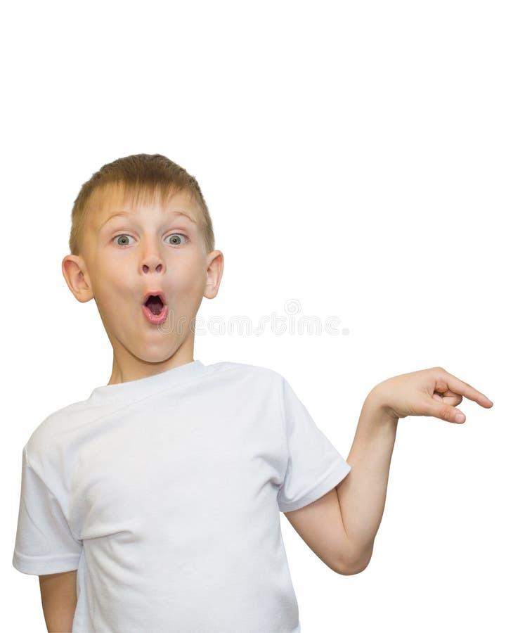 白种人青少年的男孩情感画象  看起来滑稽的少年指向和向上,当笑,隔绝在白色时 免版税库存图片