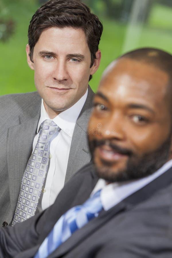 白种人&非裔美国人的商人在办公室会议 库存照片