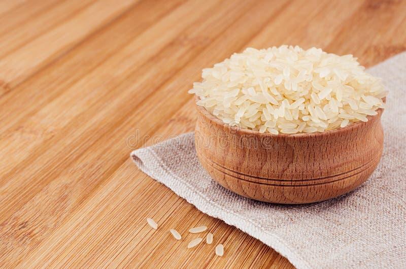 白米巴丝马香米在棕色竹板,特写镜头的木碗 土气样式,健康饮食谷物背景 免版税库存图片
