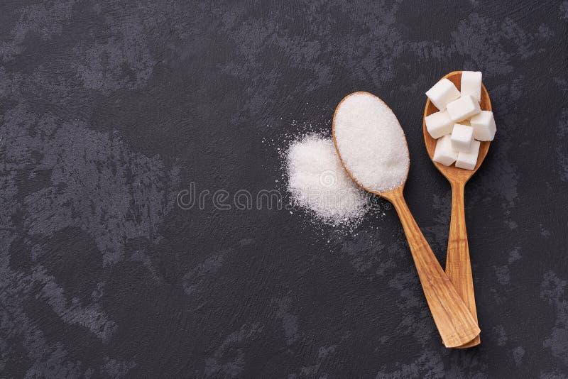 白糖立方体和砂糖在两把匙子用白糖在黑桌上 平的位置 免版税库存图片