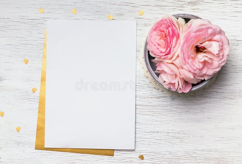 白纸和逗人喜爱的桃红色花在白色木桌上 图库摄影
