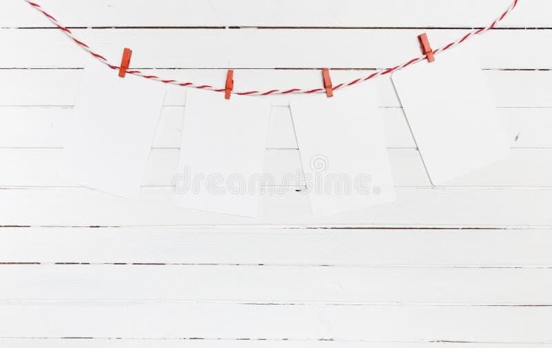 白纸或照片构筑垂悬在红色镶边晒衣绳 在木背景 您模板的文本 免版税库存照片