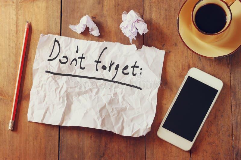 白纸的顶视图图象与文本的不在手机和咖啡杯旁边忘记handwrite,在木桌 库存照片