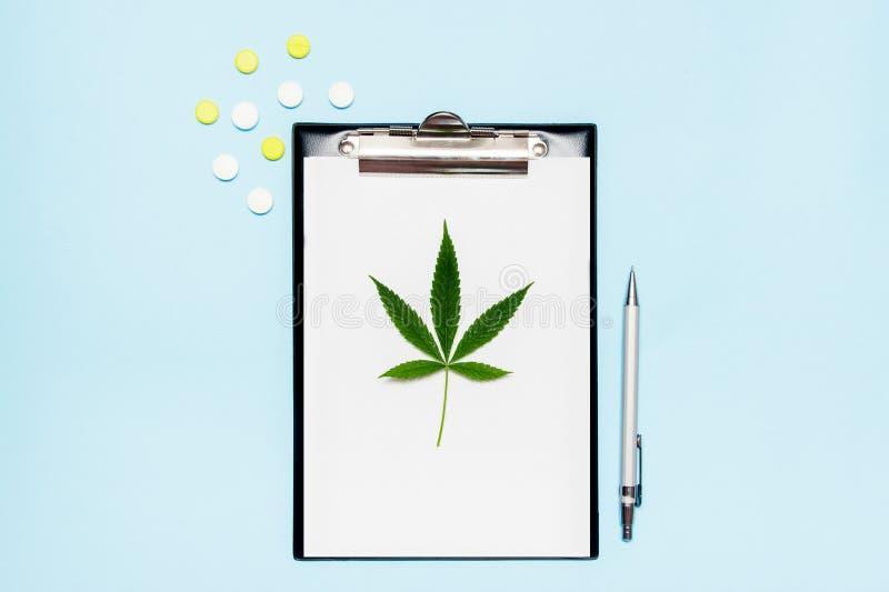 白纸顶视图写的医生处方 有医疗药片的大麻叶子在蓝色背景 ??  免版税库存图片