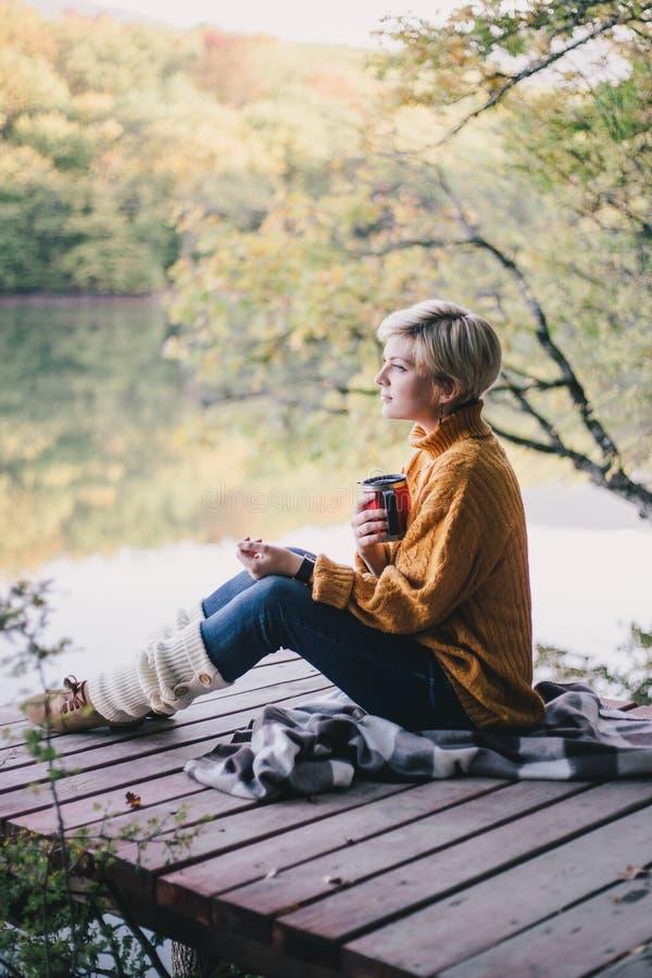 白肤金发与坐在有杯子的湖附近的蓝眼睛热的茶 免版税库存图片