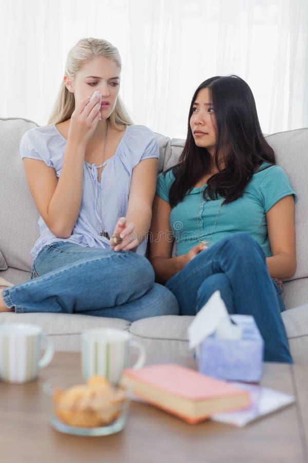 白肤金发哭泣作为她的朋友听着 免版税库存图片