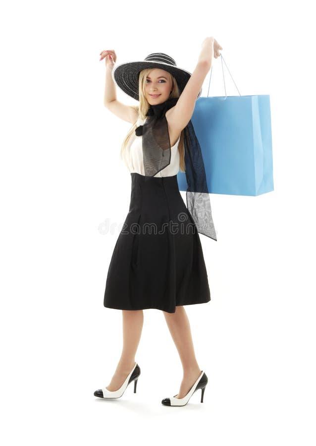 白肤金发在有蓝色购物袋的#2减速火箭的帽子 免版税库存照片