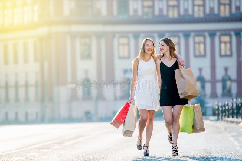 白肤金发惊人的年轻女性走在c的模型和浅黑肤色的男人 免版税库存图片